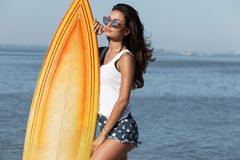 Pretty slender dark-haired girl in sunglasses dressed in a white t-shirt standing near by a yellow surfboard on the stock photo