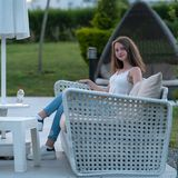Pretty Slender Young Woman Relaxing On A Patio Royalty Free Stock Photography