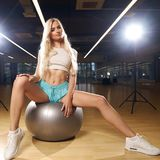 Blonde woman sitting on swiss ball Royalty Free Stock Photography