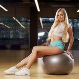 Blonde woman sitting on swiss ball. Pretty slim blonde woman with long hair, dressed in white crop top, blue shorts and trainers, sitting on silver exercise ball royalty free stock photos