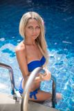 Slim blonde woman gets suntan near swimming pool. Pretty slim blonde woman suntan near the swimming pool stock images