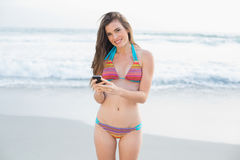 Pretty slim brown haired model in coloured bikini using a mobile phone Royalty Free Stock Photo