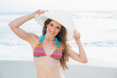 Pretty slim brown haired model in coloured bikini wearing a white hat Royalty Free Stock Photos