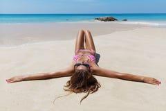 Pretty slim brunette woman in sunglasses sunbathe on the beach Royalty Free Stock Photos