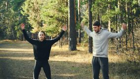 Pretty slim girl and bearded guy are exercising outdoors enjoying gymnastics warm-up in local park on sunny day. People stock video footage