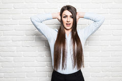 Pretty slim girl covers his ears and does not want to listen, bright photo lifestyle. Photo studio on isolated brick background Stock Photo