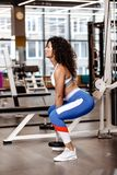 Pretty slim girl with dark curly hair dressed in a sportswear is doing back squats with heavy dumbbell in the modern gym royalty free stock photos