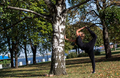 Pretty slim girl does yoga in the park. Standing at the foot of balances in the splits. Royalty Free Stock Photo