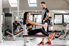 Pretty slim girl is doing exercises for the abdominals on a special exercise machine under the supervision of a coach in royalty free stock images