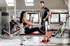 Pretty slim girl is doing exercises for the abdominals on a special exercise machine under the supervision of a coach in royalty free stock photo