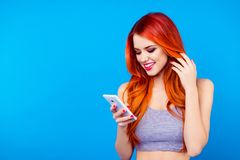 Pretty slim girl typing sms on mobile phone. Close up portrait of charming pretty lovely cheerful nice glad girl usinf downloading stock image