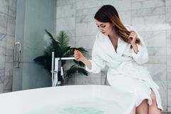 Pretty slim woman wearing bathrobe sitting on edge of bathtub filling up with water.  royalty free stock images