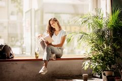 A pretty slim young girl with long hair,wearing casual outfit,sit on the windowsill and reads a book in a cozy cafe. stock images