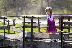 Pretty small blond long haired girl in nice red dress stands alone on old cement bridge leaning on wooden railings looking intent. Ly down on warm sunny day stock images