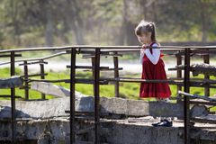 Pretty small blond long haired girl in nice red dress stands alone on old cement bridge leaning on wooden railings looking intent stock photography