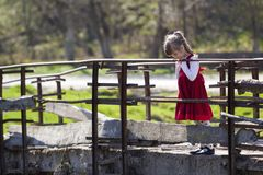 Pretty small blond long haired girl in nice red dress stands alone on old cement bridge leaning on wooden railings looking intent. Ly down on warm sunny day royalty free stock image