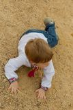 Pretty small boy closed in ukrainian shirt fall down on the sand. And preparing to stand up Stock Images