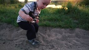 A small boy plays with a horse toy in the sand in the nature in slow motion. A pretty small boy plays with a horse toy in the sand in the nature. Action in sunny stock video