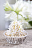 Pretty small cupcakes, lavishly decorated, on wooden table. Festive and party dessert Stock Photo
