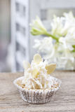 Pretty small cupcakes, lavishly decorated, on wooden table Stock Photography