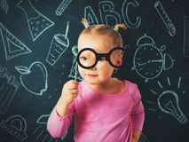 Pretty small girl investigate something through glasses on chalk. Board background, back to school theme stock photo