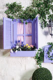 Pretty small purple window and box with flowers in an old house Stock Photography