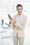 Pretty smart brown haired businesswoman using a calculator. In bright office Stock Images