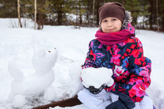 Pretty smile girl at wintertime with snow dog sculpture Royalty Free Stock Photo