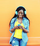 Pretty smiling african woman with headphones listens to music over orange Stock Photos