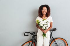 Pretty Smiling african woman posing with bicycle and flowers Stock Images