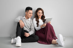 Pretty smiling asian couple in love together sitting on floor en Royalty Free Stock Photos