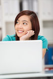 Pretty smiling Asian student sitting thinking. With her chin on her hands as she sits behind her laptop staring off to the side daydreaming Royalty Free Stock Photography