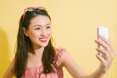 Pretty smiling asian woman using smartphone take selfie photo st stock photo