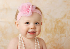 Pretty smiling baby girl. Adorable young baby girl wearing a vintage pearl necklace and pink rose headband Stock Images