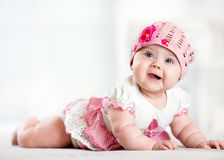 Pretty smiling baby girl lying on stomach and looking up Royalty Free Stock Photo