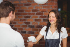 Pretty smiling barista serving a customer. At the coffee shop Stock Photo