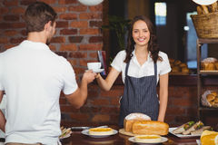 Pretty smiling barista serving a customer. Portrait of a pretty barista serving a customer at the coffee shop Royalty Free Stock Images