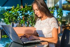 Pretty smiling blogger using laptop computer to write blogs while sitting at outdoor cafe on sunny day. Pretty smiling blogger using laptop computer to write royalty free stock image