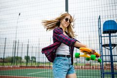 A pretty smiling blond girl wearing checkered shirt, white cap and sunglasses is walking through the sports field with a stock photography