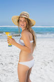 Pretty smiling blonde in bikini sipping cocktail on the beach Royalty Free Stock Photo