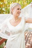 Pretty smiling blonde bride holding her veil out Stock Photos