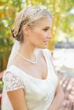 Pretty smiling blonde bride standing on a bridge Royalty Free Stock Image