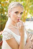 Pretty smiling blonde bride standing on a bridge looking at camera Stock Photography