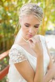 Pretty smiling blonde bride standing on a bridge looking down Stock Photo