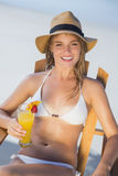 Pretty smiling blonde relaxing in deck chair on the beach with cocktail Royalty Free Stock Photos