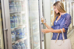 A pretty smiling blonde woman buying frozen products Royalty Free Stock Images