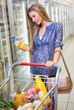 A pretty smiling blonde woman buying lemonade Royalty Free Stock Photography