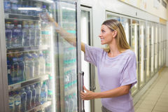 A pretty smiling blonde woman buying water Royalty Free Stock Images