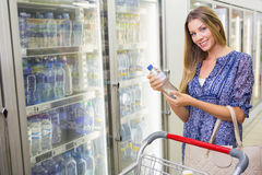 A pretty smiling blonde woman buying water Royalty Free Stock Photography