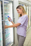 A pretty smiling blonde woman buying water Stock Image